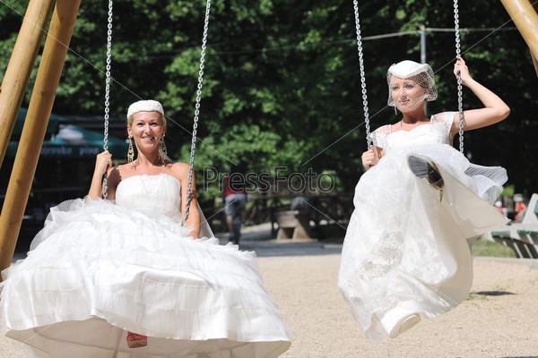 Две невесты на качелях на открытом воздухе