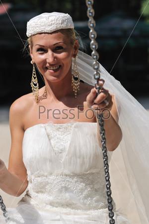 Красивая невеста на качелях на открытом воздухе