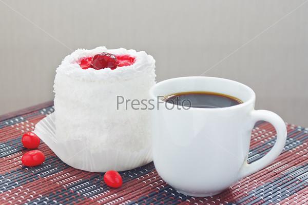 Чашка кофе и кремовый торт с вишней на столе