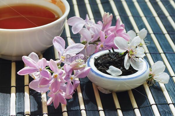 Чашка чая, баночка сухого чая, цветы вишни и сирени на бамбуковом столе