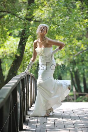 Красивая невеста в модном свадебном платье в парке