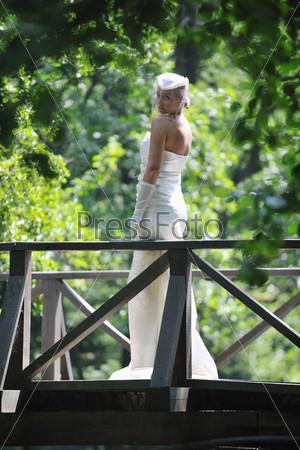 Невеста стоит на мосту в летнем парке