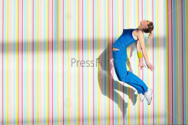 Девушка в синем спортивном костюме прыгает на фоне разноцветных полосатых обоев