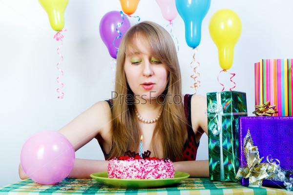 День рождения. Привлекательная девушка дует из свечи на торте