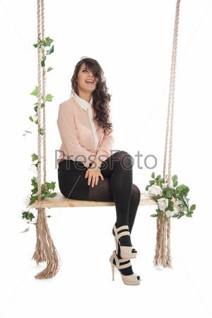 Женщина сидит на качелях