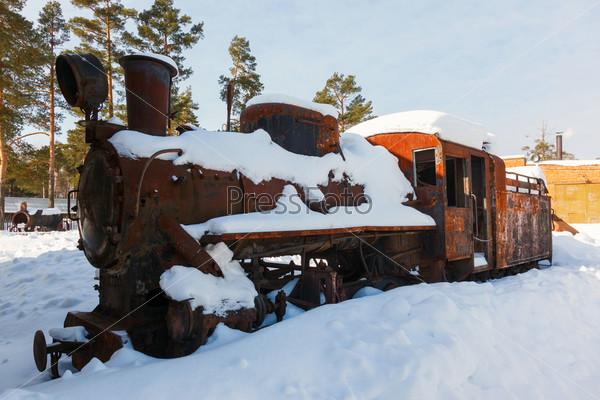 Старый сломанный локомотив в снегу