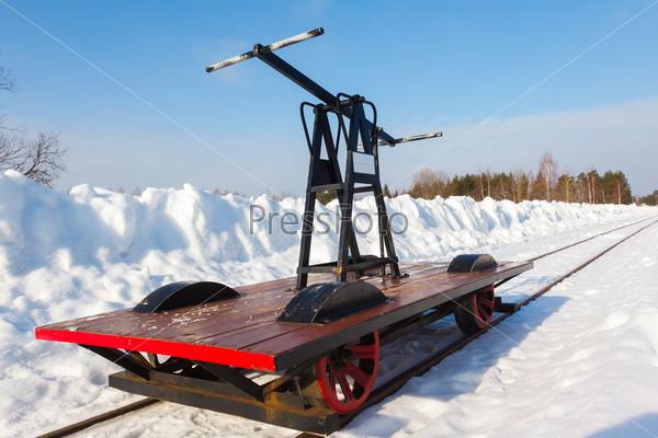 Тележка на узкой дорожке в снегу и голубое небо