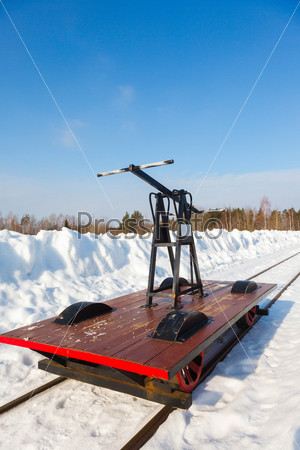 Тележка на узкой дороге в снегу и голубое небо