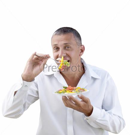Мужчина ест свежий вегетарианский овощной салат на белом фоне