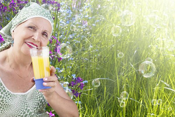 Фотография на тему Женщина с стаканом свежего апельсинового сока и спелым яблоком на  фоне зеленого солнечного луга