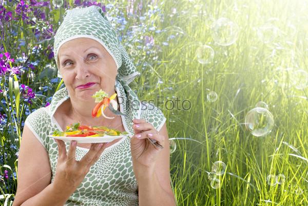 Женщина и вегетарианский свежий овощной салат на фоне летней зеленой травы