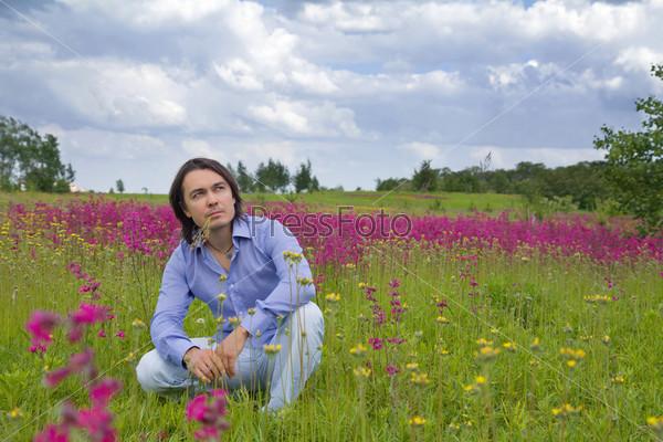 Молодой человек, сидящий на зеленом лугу