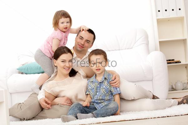 Семья лежит на ковре в гостиной