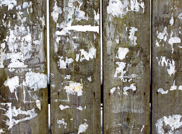 Старый деревянный забор со счищенными объявлениями
