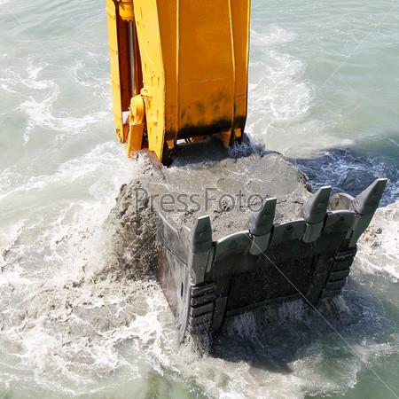Экскаватор вынимает почву с морского дна
