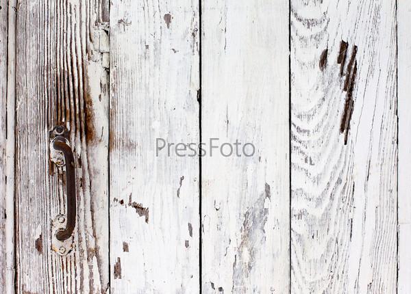 Дверь с белой краской и ржавой металлической ручкой