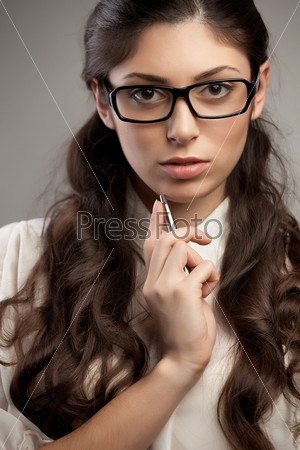 Счастливая молодая женщина улыбается и держит ручку