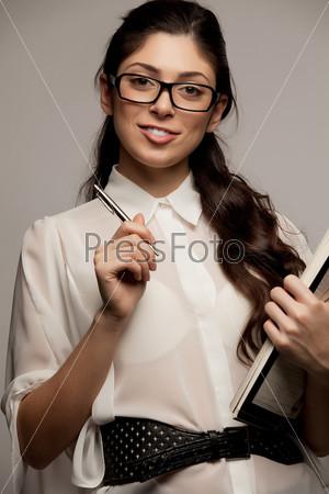 Фотография на тему Счастливая молодая женщина улыбается и держит ручку