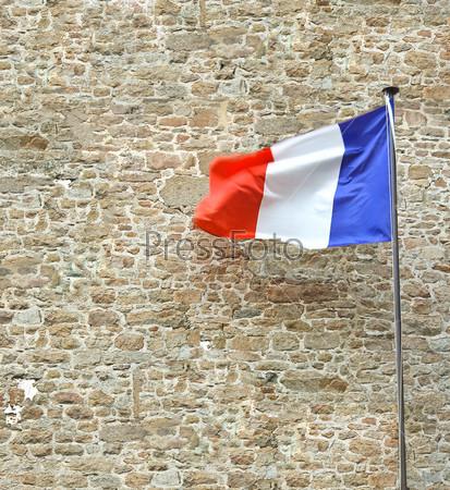 Французский флаг возле стены каменная крепость