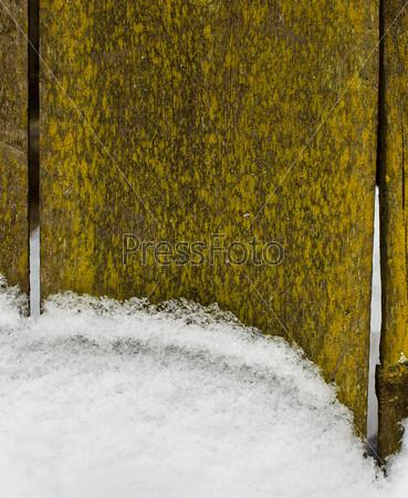 Снег у старого деревянного забора