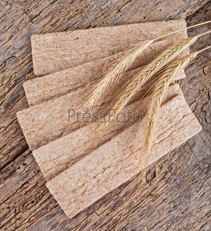 Фотография на тему Низкокалорийный хлеб с колосья пшеницы на деревянном фоне