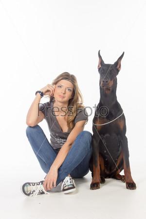 Молодая женщина с собакой породы доберман