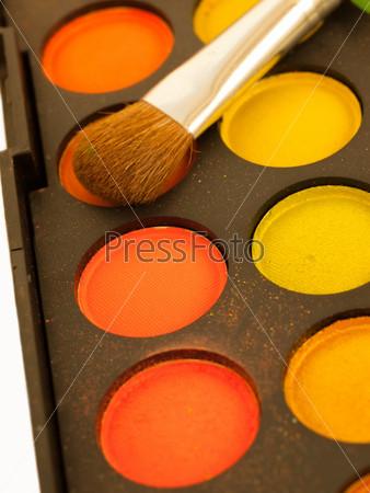 Набор разноцветных оранжево-желтых теней для век и кисть крупным планом