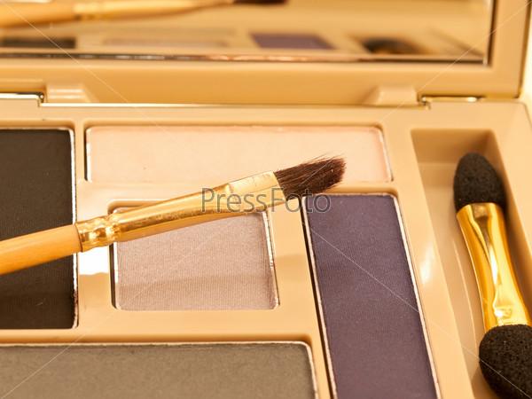 Фиолетовые и бежевые тени для век в золотой упаковке