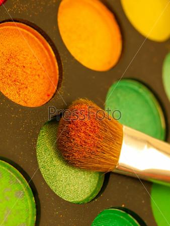 Фотография на тему Оранжево-желтые тени для век с кистью крупным планом