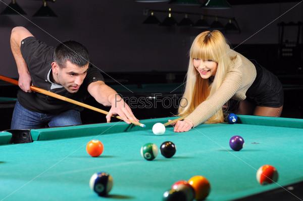 Молодая пара играет в снукер в бильярдном клубе