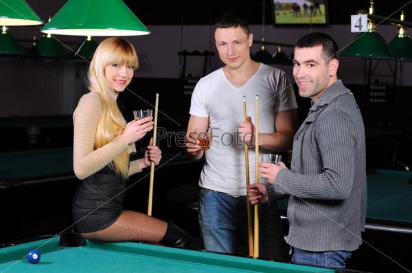 Молодые привлекательные люди играют в бильярд