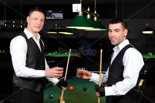 Молодые люди с напитками в руках играют в бильярд в клубе