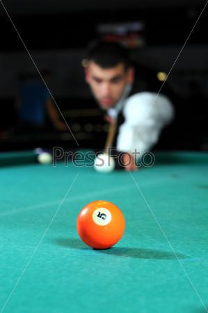 Фотография на тему Человек играет в снукер в темном клубе