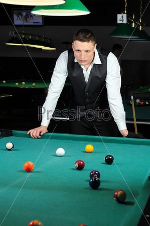 Человек играет в снукер в темном клубе