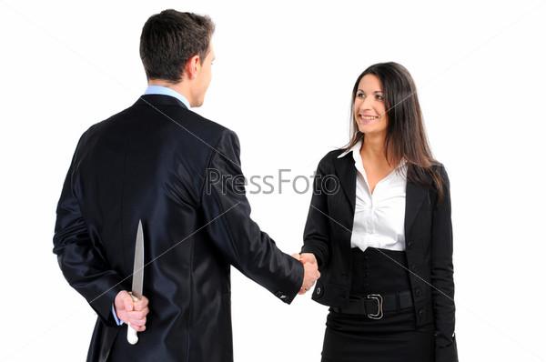 Деловые партнеры пожимают руки, мужчина держит нож за спиной