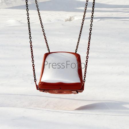 Пустые качели в зимнее время
