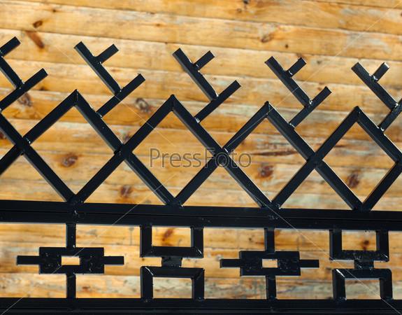 Фотография на тему Металлический черный забор с национальным орнаментом на фоне деревянной стены