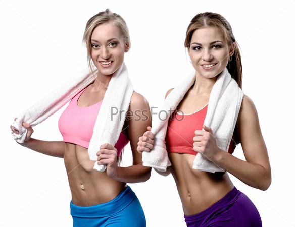Две красивые девушки после тренировки с полотенцами, изолированные на белом фоне