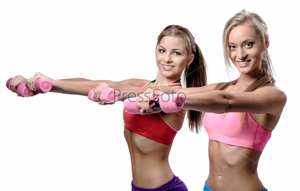 Две красивые девушки делают упражнение с гантелями