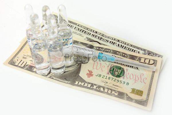 Ампулы с лекраством и шприц на долларах