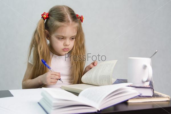 Девочка листает книгу и пишет конспект на листе бумаги, сидя за столом