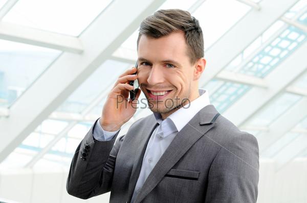 Молодой парень наслаждается разговором по мобильному телефону