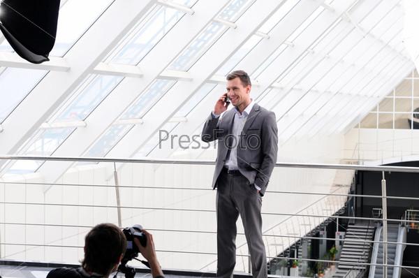 Фотограф снимает делового мужчину с телефоном
