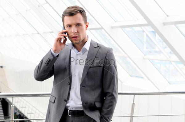 Фотография на тему Молодой парень наслаждается разговором по мобильному телефону
