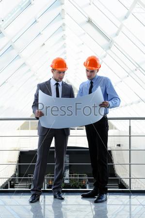 Двое мужчин в касках на строительной площадке