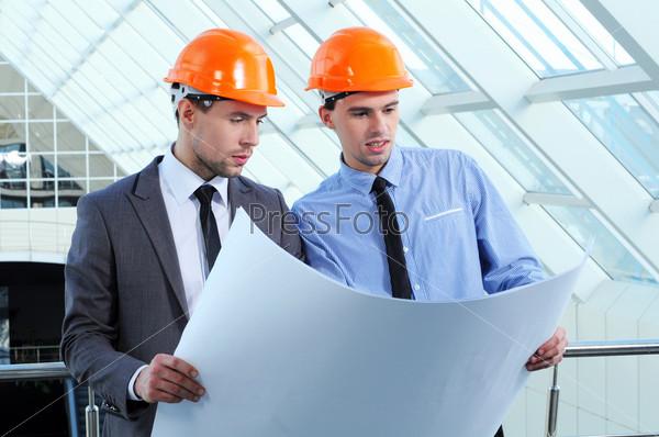 Фотография на тему Двое мужчин в касках на строительной площадке