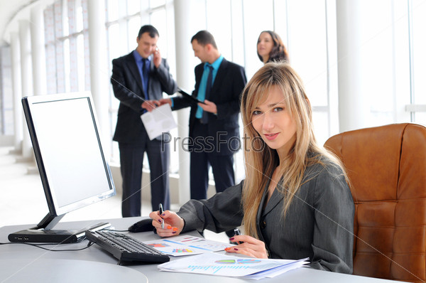 Симпатичная европейская бизнес-леди за рабочим столом с коллегами на заднем плане