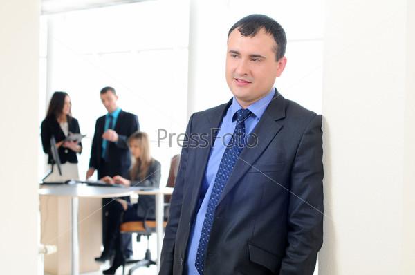 Красивый деловой человек и его коллеги на заднем плане