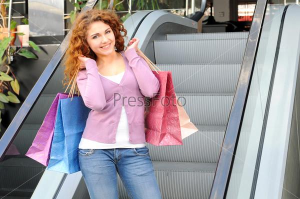Фотография на тему Красивая женщина с покупками на эскалаторе