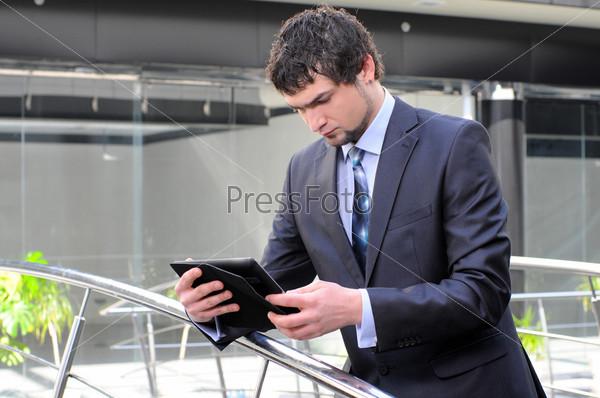 Фотография на тему Мужчина использует электронный планшет перед современным зданием